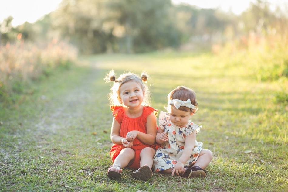 Girls sitting in a grass   Outdoor Family Session by Bára Miller Photography