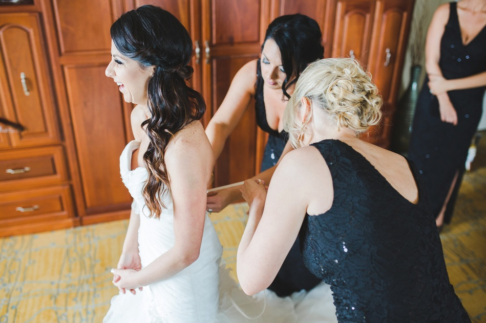 Bride getting into her wedding gown and laughing at Tampa Waterside Marriott